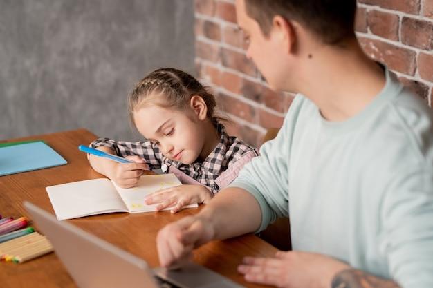 Inhoud schattige dochtertje met vlecht aan tafel zitten en tekening in notitieblok tonen aan vader die met laptop thuis werkt