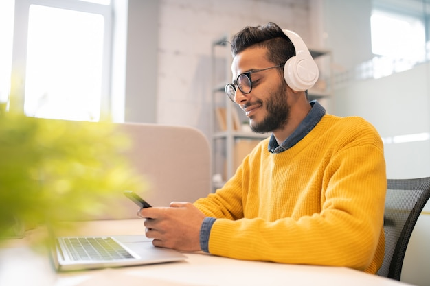 Inhoud tevreden jonge arabische man met baard zitten in moderne kantoren en messaging in smartphone tijdens het werken op kantoor