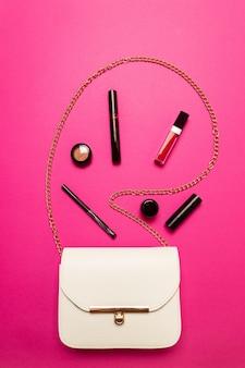 Inhoud van een witte vrouwelijke tas. vrouwelijke tas met kopie ruimte op roze achtergrond
