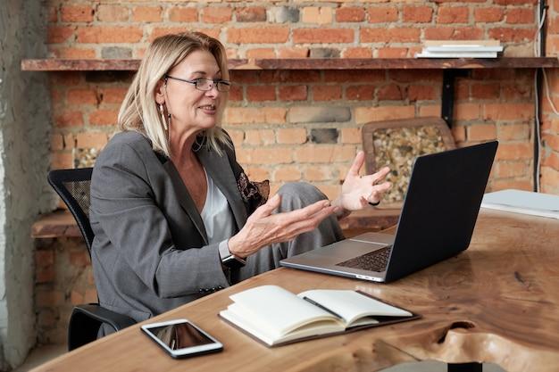 Inhoud volwassen dame geïnspireerd door eigen ides die haar plan presenteert tijdens videoconferenties met zakenpartner met behulp van laptop