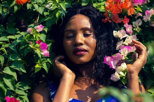 Inhoud zwarte vrouw ruiken met bloemen in park.