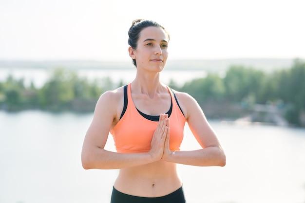 Inhoudelijke energieke yoga-coach in sportbeha die namaste-gebaar buitenshuis maakt terwijl hij studenten verwelkomt bij de praktijk