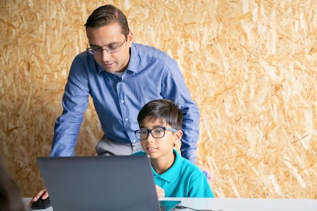 Inhoudleraar die op middelbare leeftijd aan jongen met les helpt en thema uitlegt