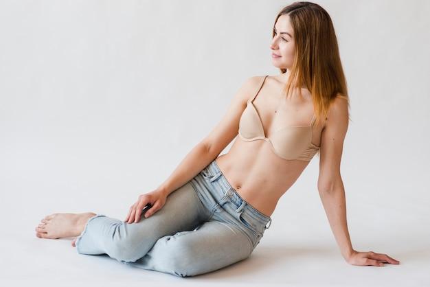 Inhouds roodharige vrouw in bustehouder en jeans