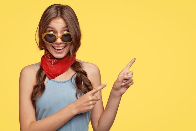 Inhoudsgevoelige vrouw heeft donker haar in vlechten gekamd, lacht vrolijk, wijst met beide wijsvingers opzij, toont plaats voor het maken van boodschappen met grote kortingen, maakt reclame voor artikel. hé, kijk hier eens!
