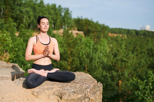 Inhoudsvrije jonge vrouw in sportkleding zittend met gekruiste benen en energie voelen met meditatie in de bergen