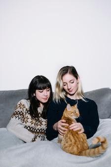 Inhoudsvrouwen die met kat op laag koelen