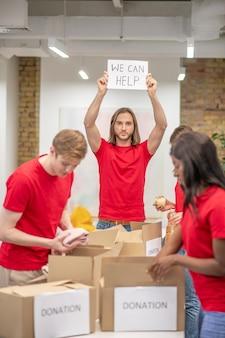 Initiatief. jonge optimistische kerel die poster in opgeheven handen met inscriptie en collega's vrijwilligers verpakking donatie dozen