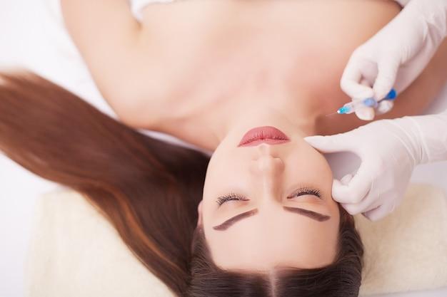 Injectie en vrouw schoonheid gezicht. aantrekkelijk meisje met perfecte huid. vrouw in spa, masseer de rug, gladde huid. schoonheid en jeugdigheid van de huid, gezichtsbehandelingen in de schoonheidssalon