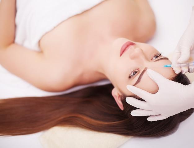 Injectie en vrouw schoonheid gezicht. aantrekkelijk meisje met perfecte huid.