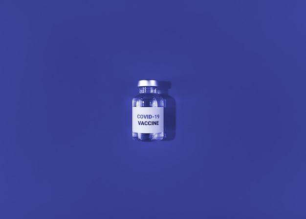 Injectieflacon met covid 19-vaccin op een blauwe kleur