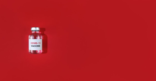 Injectieflacon met covid19-vaccin op een rode kleur