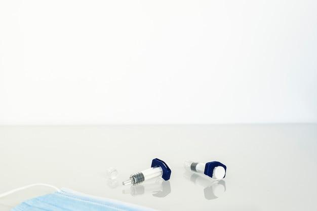 Injectieflacon met medicijnen op witte glazen tafel