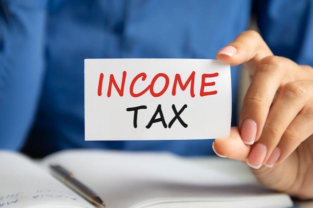 Inkomstenbelasting is geschreven op een wit visitekaartje in de hand van een vrouw. blauwe achtergrond. bedrijfs- en reclameconcept
