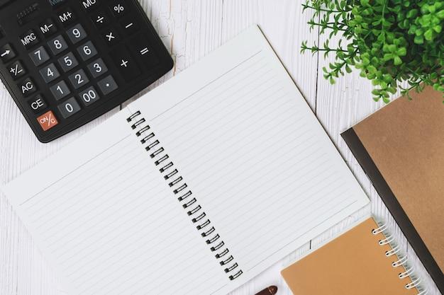 Inkt pen met notebookpapier en rekenmachine op hout