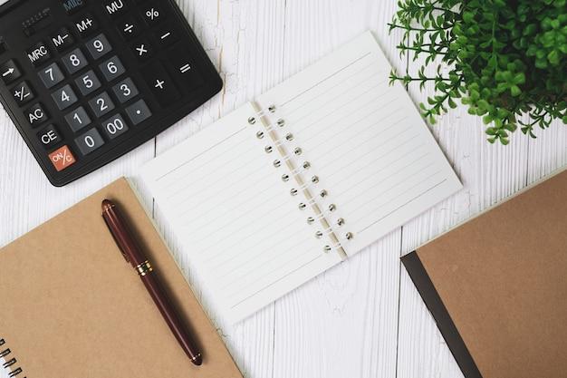 Inkt pen met notebookpapier en rekenmachine op woode