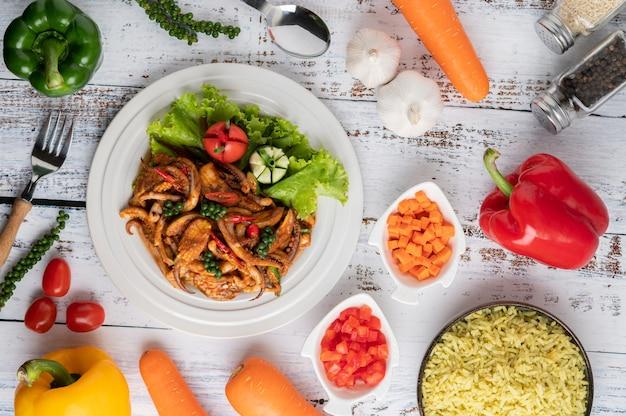 Inktvis gebakken met currypasta in witte plaat, met groenten en bijgerechten op een witte houten vloer.