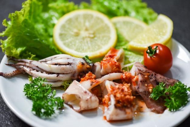 Inktvis salade met chili saus pittige kruiden en specerijen / gegrilde inktvis slice op plaat in het visrestaurant