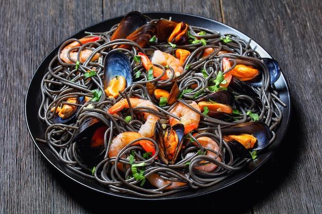Inktvispasta met zeevruchten: mosselen en garnalen op een zwarte plaat op een donkere houten ondergrond, bovenaanzicht, close-up