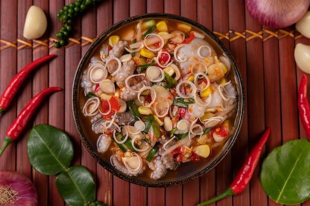 Inktvissalade met koriander, gehakte groene ui, knoflook en mais op het bord