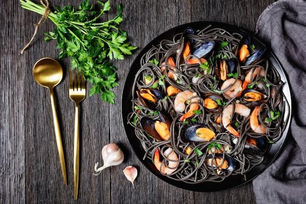 Inktvisspaghetti met zeevruchten: mosselen en garnalen op een zwarte plaat met gouden bestek op een donkere houten ondergrond, bovenaanzicht, close-up