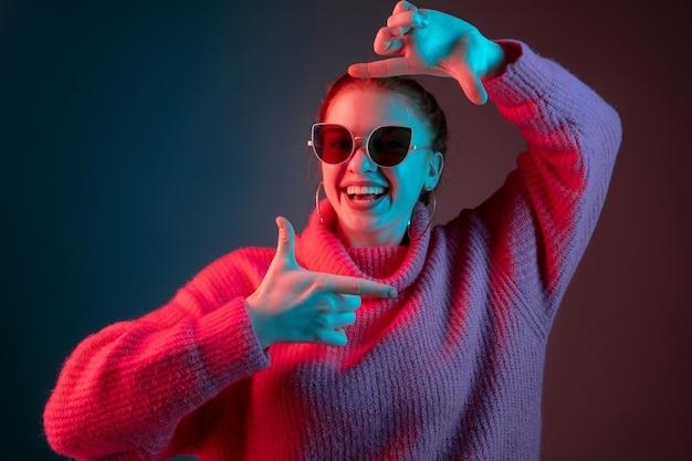 Inlijsten. het portret van de blanke vrouw geïsoleerd op de achtergrond van de gradiëntstudio in neonlicht. mooi vrouwelijk model met zonnebril, rood haar. concept van menselijke emoties, gezichtsuitdrukking, advertentie.