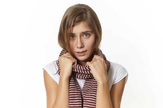 Inluenza, verkoudheid, infectie, virus en gezondheidsconcept. foto van schattige gefrustreerde jonge vrouw die gebreide warme sjaal draagt die zich ziek voelt, keelpijn heeft, haar blik pijn en vermoeidheid uitdrukt