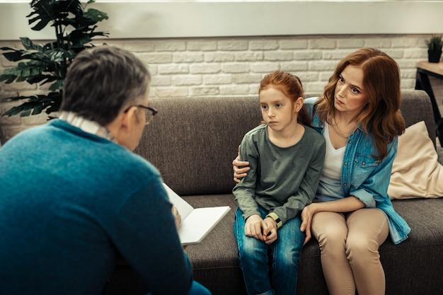 Innerlijk conflict. triest, ongezellig meisje dat naar de psycholoog kijkt terwijl ze bij haar moeder zit