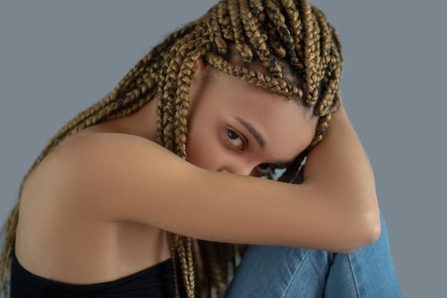 Innerlijke pijn. droevige jonge afrikaanse amerikaan die haar knie vasthoudt en haar hoofd in haar arm verbergt