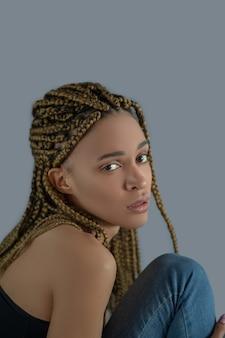 Innerlijke pijn. teleurgestelde jonge afro-amerikaanse vrouwenzitting, die haar knie vasthoudt
