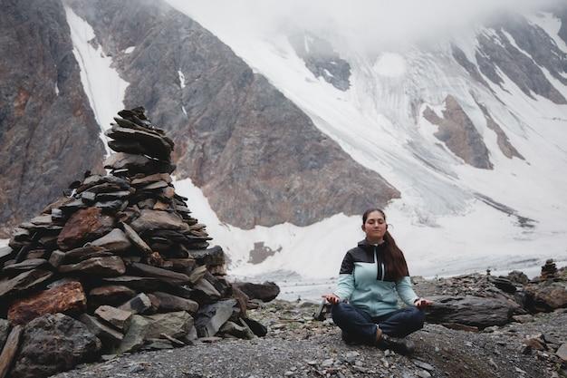 Innerlijke rust en zorgzaamheid. een vrouw mediteert met een prachtig uitzicht op de met sneeuw bedekte bergen. aktru glacier highlands