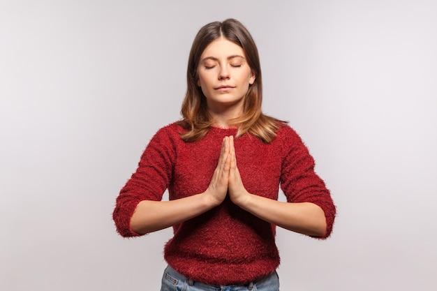 Innerlijke rust, zen beoefening. portret van een kalm meisje dat haar geest concentreert, handen vasthoudt namaste