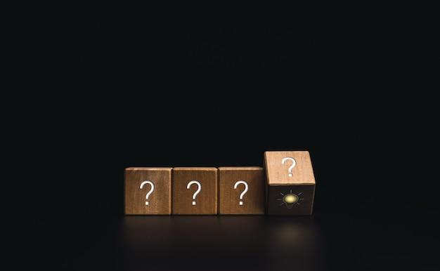Innovatie, conclusie, slim leren, kennis en creatief idee concept. flipping houten kubusblok met gloeilamp symbool met vraagteken probleempictogram op donkere achtergrond, minimalistische stijl.
