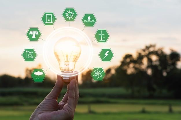 Innovatie en energieconcept van de hand houdt een gloeilamp en kopieert ruimte voor tekst invoegen.