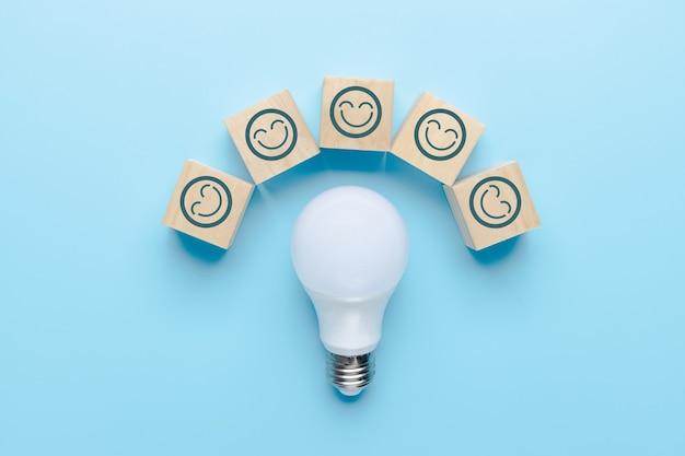 Innovatie en ideeconcept, glimlachpictogram op kubusdoos met gloeilamp op blauwe achtergrond
