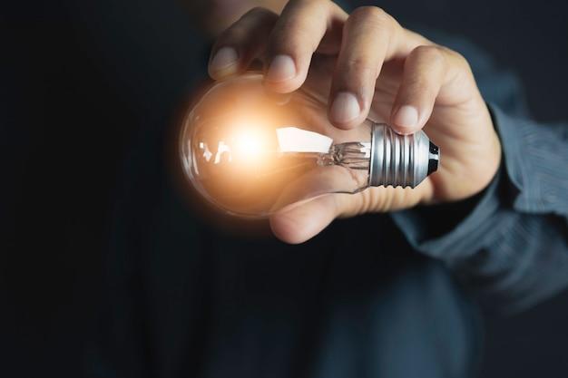 Innovatie of creatief concept van de hand houdt een gloeilamp en kopie ruimte voor invoegen tekst.