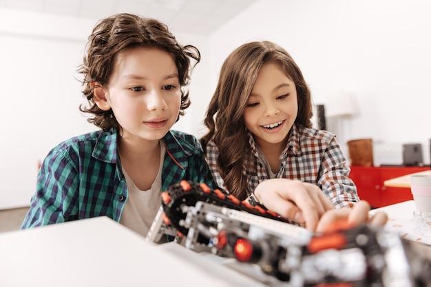 Innovatief robotsysteem testen. positief opgetogen geïnspireerde vrienden die in het wetenschapslokaal zitten en robot gebruiken tijdens het programmeren