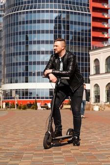 Innovatieve transport blije optimistische man leunend op elektrische scooter