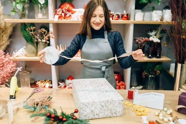 Inpak- en decoratieproces voor kerstcadeaus. vrouw wraps aanwezig op tafel, decorprocedure, feestelijk pakket