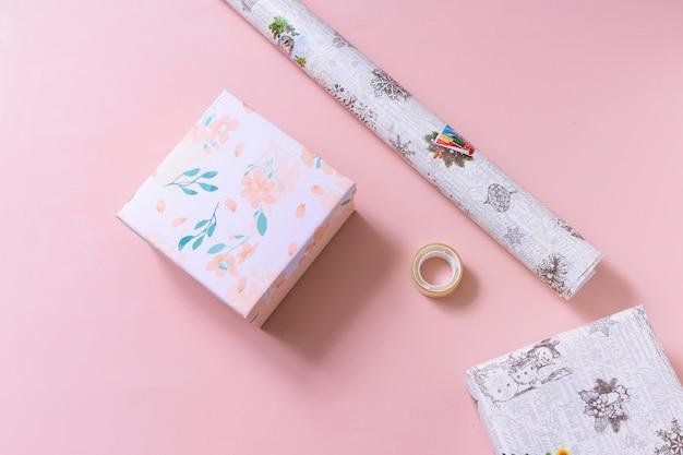 Inpakpapier, tapes en dozen op roze. plat leggen