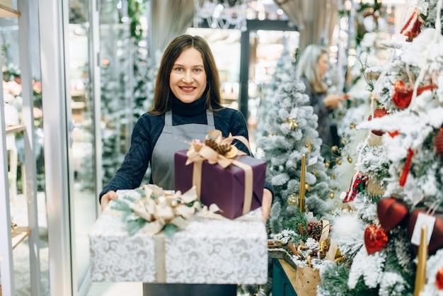 Inpakservice verkoper met feestelijke geschenkdozen, professionele handgemaakte decoratie.