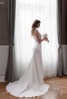 Inschrijving blonde kaukasische bruid in stijlvolle jurk met witte bruiloft boeket staat in de buurt van het raam