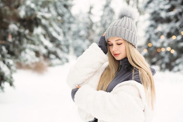 Inschrijving blonde vrouw in een witte jas wandelen in het bos van de winter. ruimte voor tekst