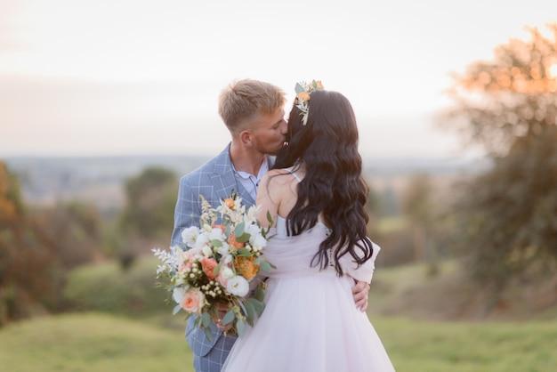 Inschrijving bruid en bruidegom kisssing buiten in de avond op de weide met prachtige bruiloft boeket