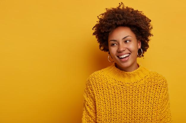 Inschrijving charmante gelukkig gekrulde vrouw heeft vreugdevolle gezichtsuitdrukking ontspannen, afro kapsel, draagt gebreide trui, lacht enthousiast, vormt tegen gele achtergrond