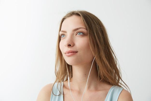 Inschrijving dromerig jong mooi meisje dromen luisterend naar het streamen van muziek in de koptelefoon.