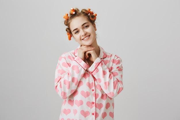 Inschrijving en schattig glimlachend meisje in pyjama's en haarkrulspelden