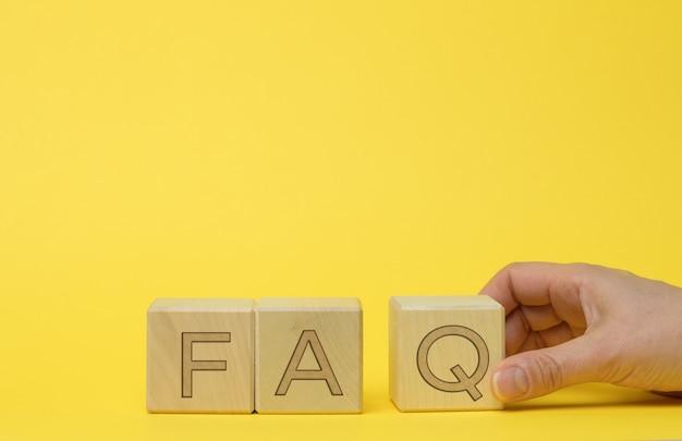 Inschrijving faq (veelgestelde vragen) op houten blokken. vraag- en antwoordconcept, hulp en tips