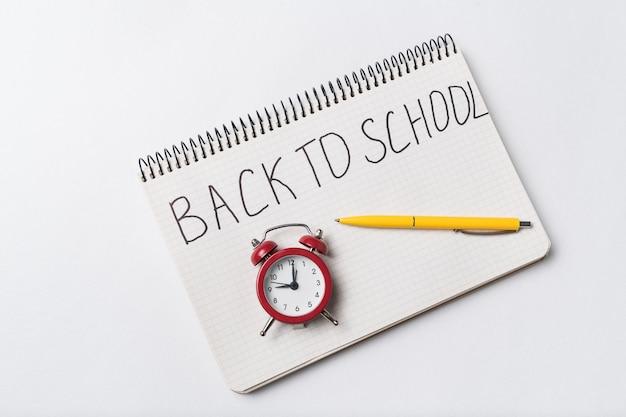 Inschrijving in beurtboek terug naar school. vintage wekker en pen. bovenaanzicht