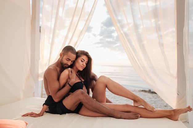 Inschrijving jong koppel ontspannen in bed op het strand samen